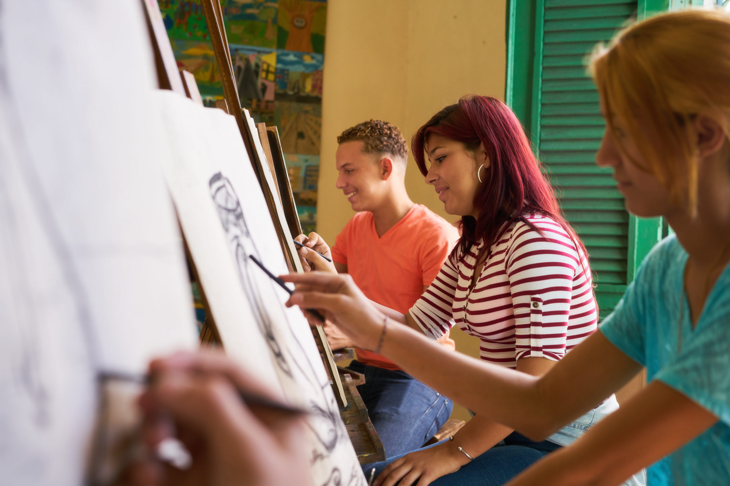 Three art students drawing on easels
