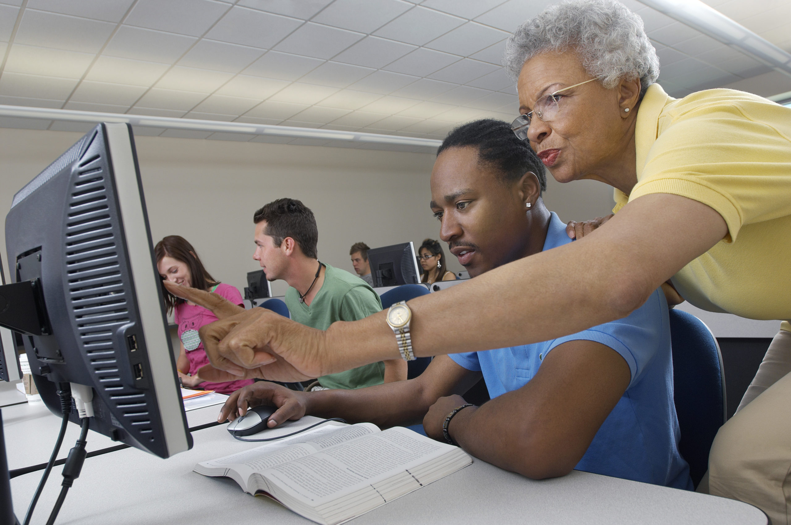 Senior teacher assisting male student during computer class with classmates in the background