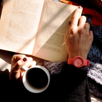 A person holding a coffee cup with a book in her lap
