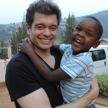 Michael Stromme holding a child, both are smiling widely